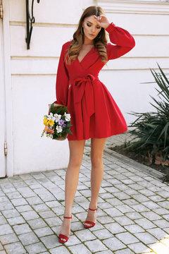 beautiful woman with dark hair in elegant red dress walking by the street