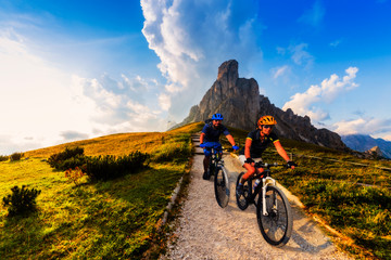Wall Mural - Cycling woman and man riding on bikes in Dolomites mountains landscape. Couple cycling MTB enduro trail track. Outdoor sport activity.