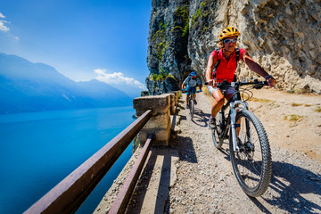 Wall Mural - Cycling woman and man riding on bikes at sunrise mountains and Garda lake landscape. Couple cycling MTB enduro flow sentiero ponale trail track. Outdoor sport activity.