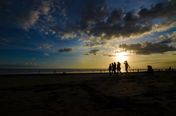 Five girls walking next to a couple while Sunset at Double Six Beach, Legian, Seminyak, Kuta, Bali, Indonesia