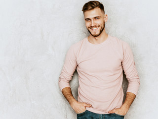 Portrait of handsome smiling hipster lumbersexual businessman model wearing casual summer pink clothes. Fashion stylish man posing against gray wall - fototapety na wymiar