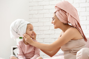 Cute little daughter with her mother after shower sitting on bed