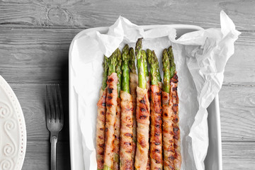 Baking dish with bacon wrapped asparagus on wooden table