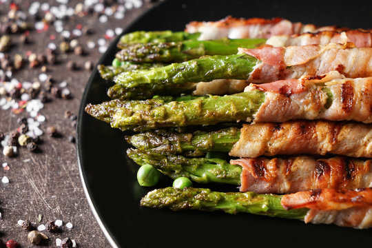 Plate with bacon wrapped asparagus on grey table, closeup