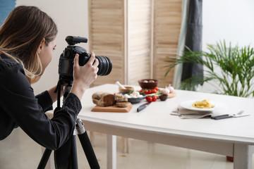 Female food photographer working in home studio