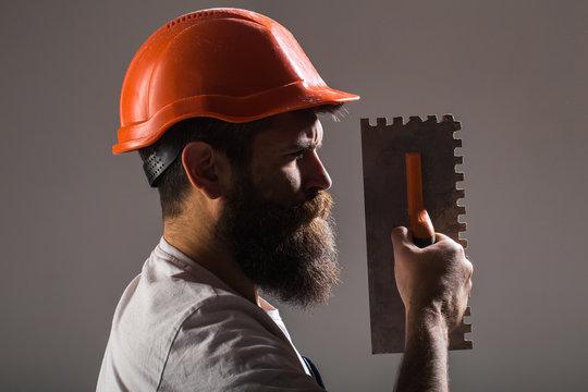 Tool, trowel, handyman, man builder. Mason tools, builder. Builders in hard hat, helmet. Bearded man worker, beard, building helmet, hard hat. Mason plastering concrete to build. Plastering tools.