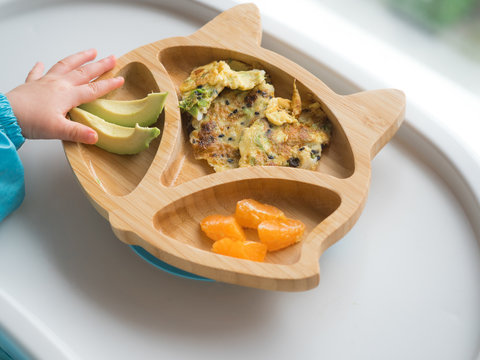 Baby eating by hands, Baby eating organic bio vegetables with BLW method, baby led weaning. Happy vegetarian kid. Toddler eat himself, self-feeding. infant baby eating. Omelette with orange, avocado