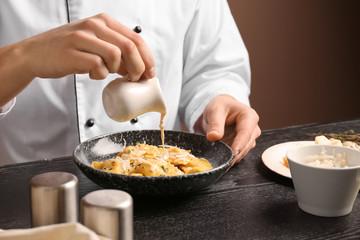Male chef preparing for serving tasty ravioli on table