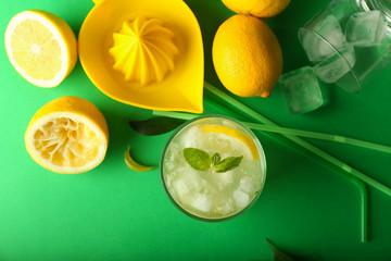 Glass of tasty cold lemonade on color background