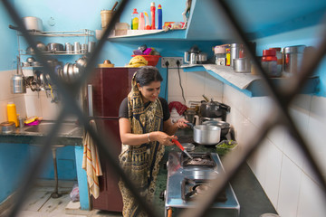 Indian Woman In Kitchen Cooking Food