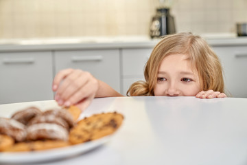 Child secretly taking american cookies from plate.