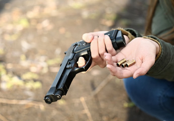 Young depressed woman with gun and bullets thinking about suicide outdoors