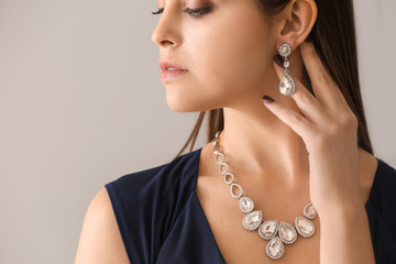Young woman with beautiful jewelry on light background