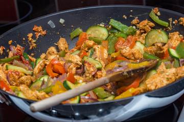 Close up of chciken adn pepper stir fry in a wok with a wooden spoon