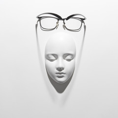 Plaster face mask with elegant glasses above it on a white background with soft long shadows, copy space. Flat lay.