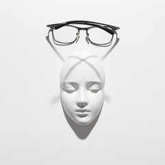 Gypsum face sculpture with elegant glasses with long crossing shadows on a white background, copy space. Top view.
