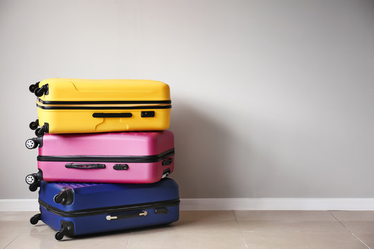 Packed suitcases near light wall