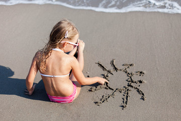 Kid is drawing sun in sand at beach. Concept of children picture, sand painting at summer vacation, holiday and travel. Little girl is sitting in waves outdoors. Child is enjoying summertime.