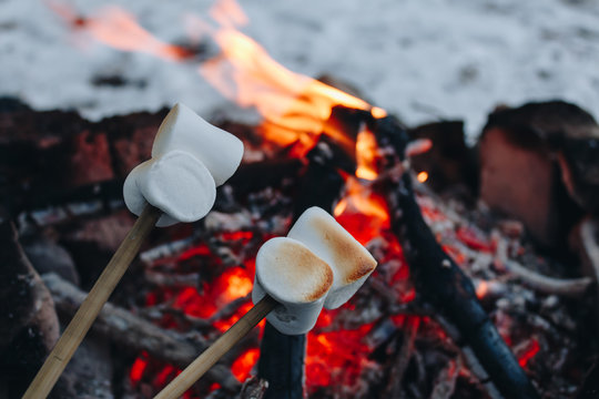 Roasted marshmallows on a fire in the winter forest