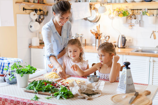 Family are cooking italian pizza together in cozy home kitchen. Cute kids with happy mother are preparing food or meal for dinner. Two girls are helping woman. Children chef concept.