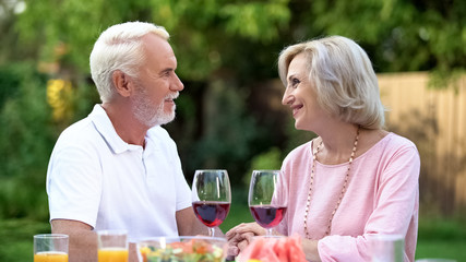 Old couple celebrating anniversary, drinking wine, everlasting love relations