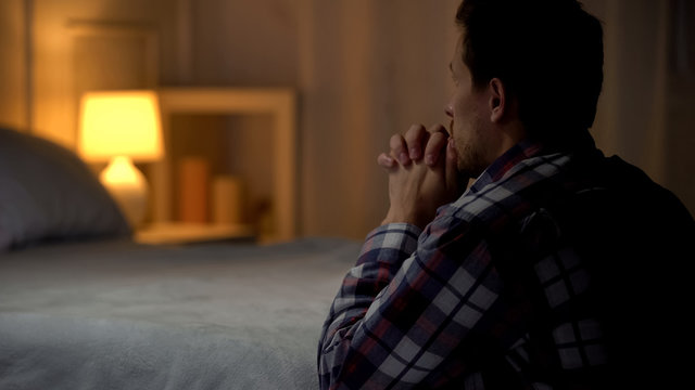 Man kneeling near bed and praying to god, thanking for life opportunities