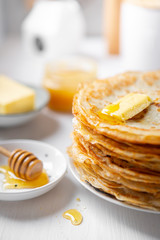A stack of thin russian pancakes with butter and honey on a white plate