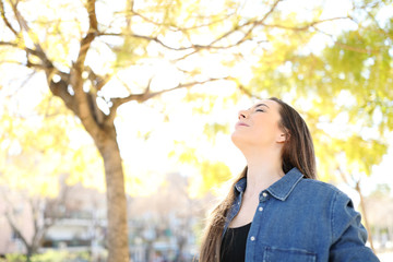 Relaxed woman is breathing fresh air in a park