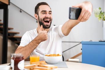 Handsome young man having breakfast