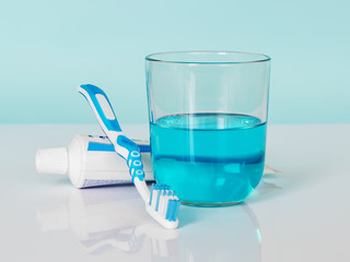 Toothbrush, toothpaste, mouthwash on a white-blue background. The concept of daily dental care.