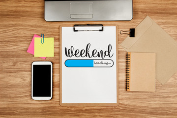 Weekend loading text on white sheet and office supplies on wooden table