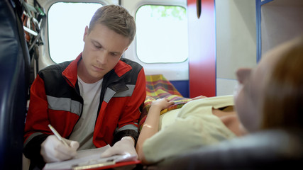 Doctor filling out medical form in ambulance, emergency help to female patient