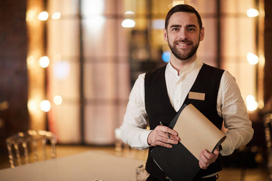 Waist up portrait of handsome waiter smiling cheerfully at camera standing in luxury restaurant or cafe, copy space