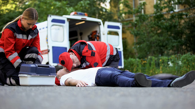 Doctors helping unconscious man on road, emergency care to car accident victim