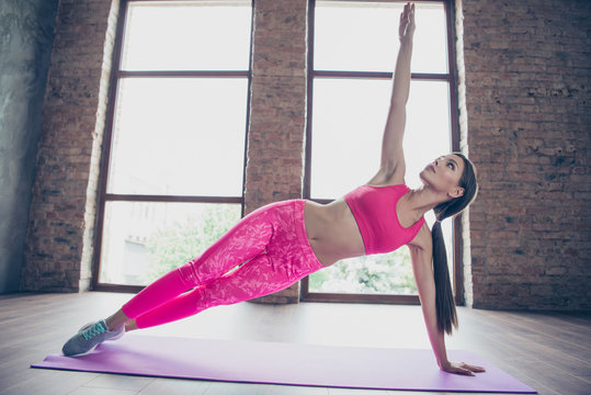 Full length body size of nice attractive winsome charming adorable sportive thin perfect shape form lady wearing pink clothes top warming-up raising hand up in modern loft industrial interior