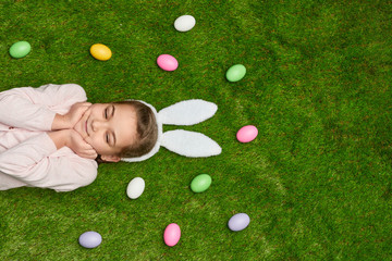 Dreaming girl lying on lawn with Easter eggs