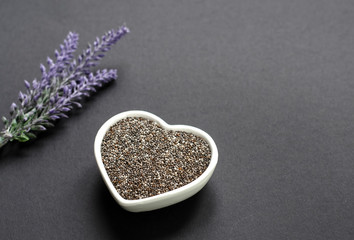 Organic chia seeds in a white heart bowl on black surface with lavander flower decoration