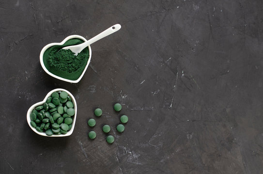 Green algae spirulina powder and tablets in small white heart containers