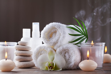 Fototapeta Aromatherapy, spa, beauty treatment and wellness background with massage pebbles, orchid flowers, towels, cosmetic products and burning candles. obraz