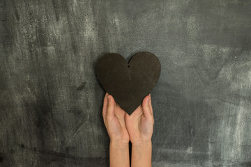 kids hands on a chalkboard background holding a wooden heart