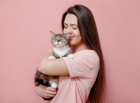 young attractive woman hugging cat in hands, pink background