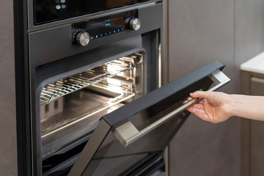 Woman hand opening built-in oven in black kitchen cabinet