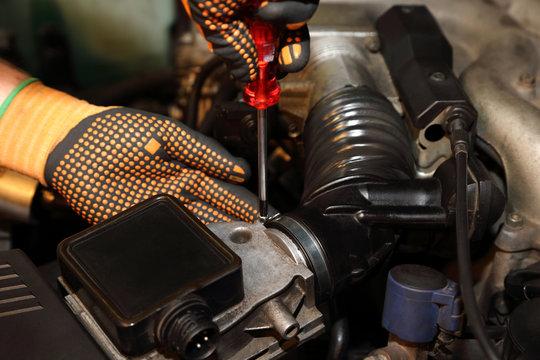 Montaż filtra powietrza w samochodzie osobowym, dokręcanie obejmy.