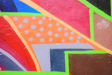 Detail of an anonymous street graffiti with many colors, cheerful urban background.