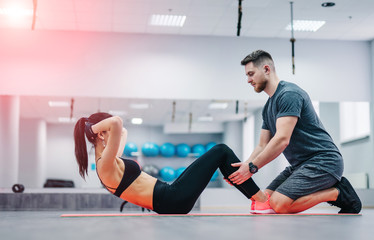 Woman doing abdominal crunches press exercise on the mat with her sports male trainer in gym. Couple exercises on the blurred background of the gym.