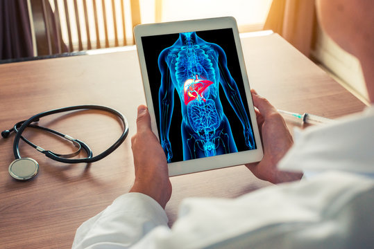 Doctor holding a digital tablet with x-ray of body skeleton with liver. Stethoscope and syringe on the desk