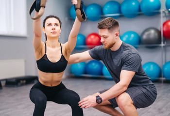 Muscular beardy trainer helping attractive female to practice with TRX in the fitness center. Sporty woman doing exercises with personal instructor at gym. Close-up