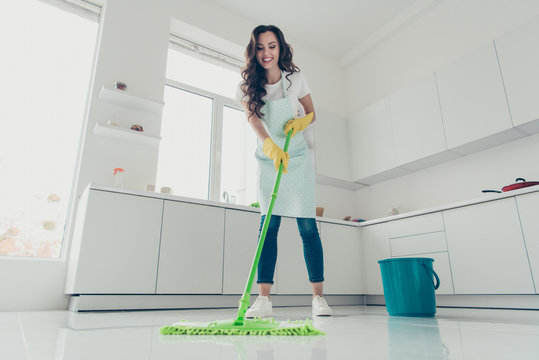 Full length body size low angle view photo beautiful busy cheerful hardworking duties she her lady house glad love clean house wear jeans denim casual t-shirt covered cute apron bright light kitchen