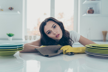 Portrait of her she nice lovely beautiful glamorous sad puzzled wavy-haired house-wife done plates piles on table in modern light white interior indoors
