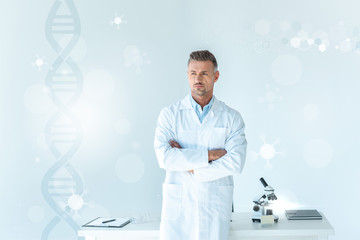 handsome scientist standing with crossed arms near table on white with dna